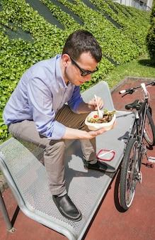 Młody biznesmen je sałatkę w przerwie obiadowej, siedząc na ławce na świeżym powietrzu