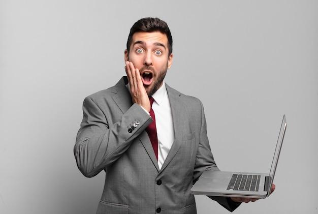 Młody biznesmen jest zszokowany i przestraszony, wygląda na przerażonego z otwartymi ustami i dłońmi na policzkach i trzyma laptopa