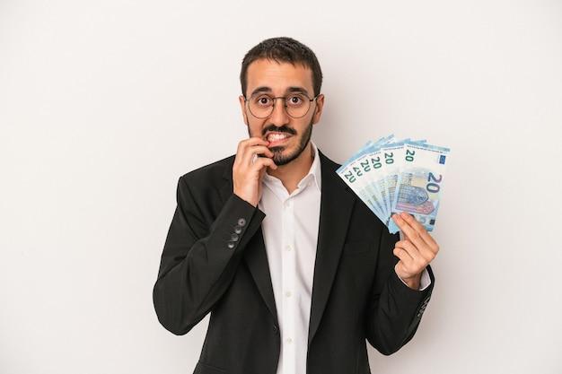 Młody biznesmen kaukaski gospodarstwa banknotów na białym tle gryzie paznokcie, nerwowy i bardzo niespokojny.