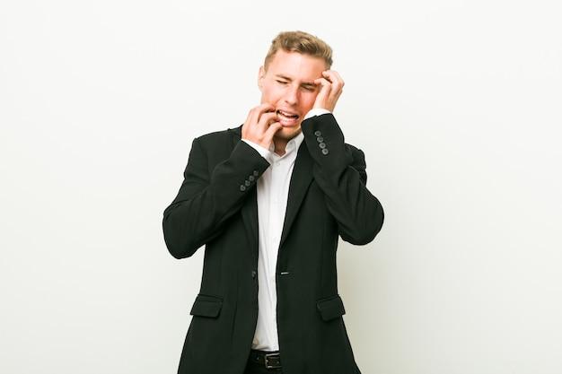 Młody biznesmen kaukaski jęczy i płacze niepocieszony.