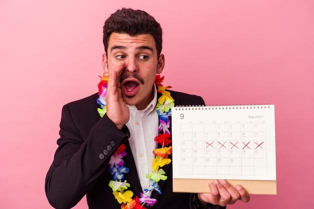 Młody biznesmen kaukaski liczący dni na wakacje na białym tle na różowym tle mówi tajne gorące wiadomości o hamowaniu i patrząc na bok