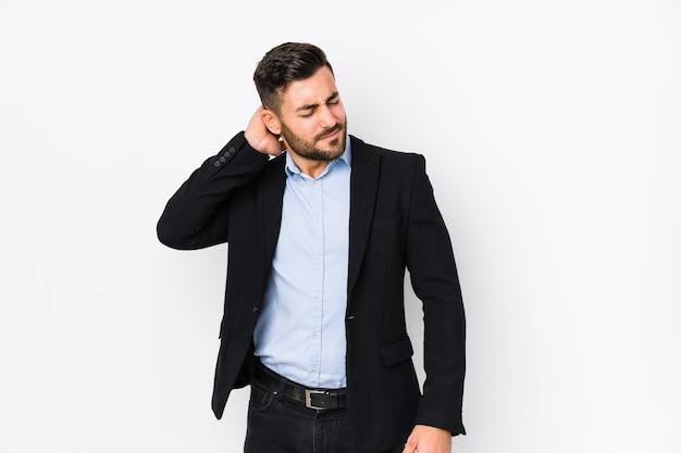 Młody biznesmen kaukaski na białym tle na białym tle cierpi na ból szyi z powodu siedzącego trybu życia.