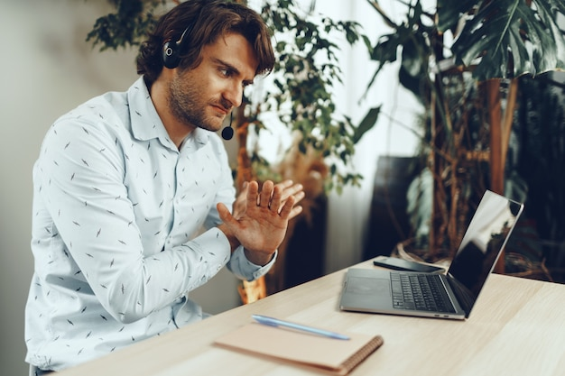 Młody biznesmen kaukaski posiadania połączenia wideo z partnerami klientów