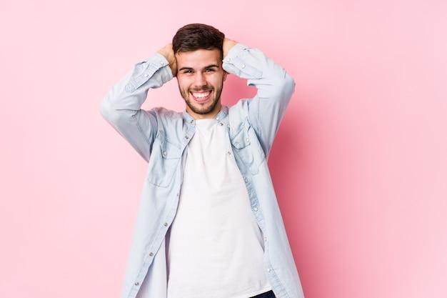 Młody biznesmen kaukaski pozowanie w białej ścianie na białym tle śmieje się radośnie trzymając ręce na głowie. koncepcja szczęścia. <mixto>