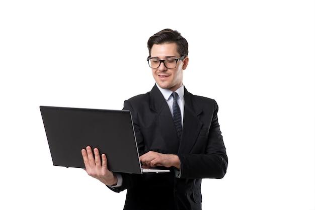 Młody biznesmen krawat i czarny garnitur za pomocą laptopa, samodzielnie na białym tle