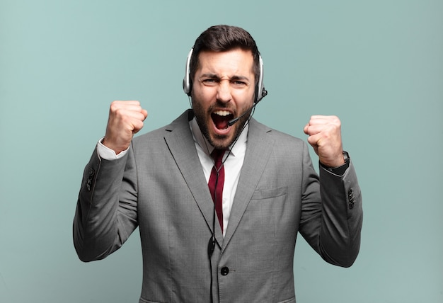 Młody biznesmen krzyczy agresywnie z gniewnym wyrazem twarzy lub z zaciśniętymi pięściami świętuje sukces koncepcji telemarketingu