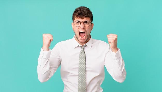Młody biznesmen krzyczy agresywnie z gniewnym wyrazem twarzy lub z zaciśniętymi pięściami świętuje sukces