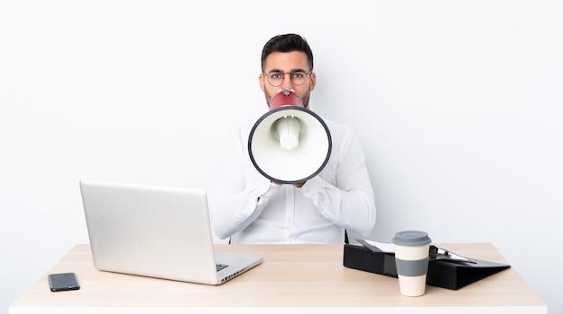 Młody biznesmen krzyczy przez megafon w miejscu pracy