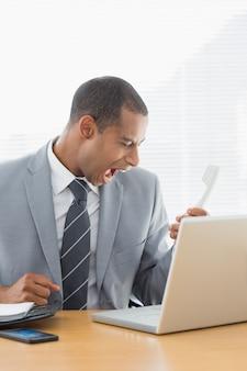 Młody biznesmen krzyczy w telefon przy biurem