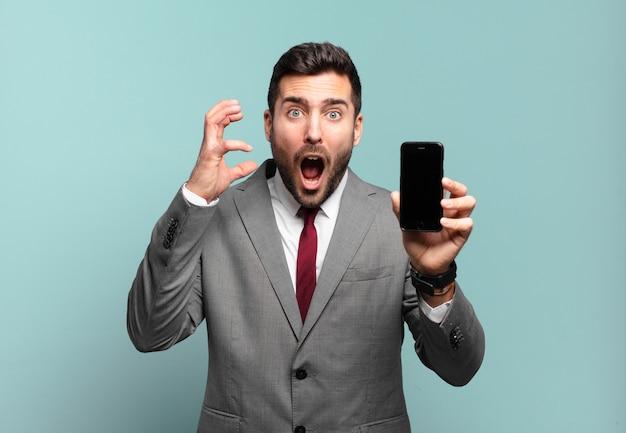 Młody biznesmen krzyczy z rękami do góry, czuje się wściekły, sfrustrowany, zestresowany i zdenerwowany oraz pokazuje ekran swojego telefonu