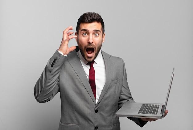Młody biznesmen krzyczy z rękami do góry, czuje się wściekły, sfrustrowany, zestresowany i zdenerwowany oraz trzyma laptopa