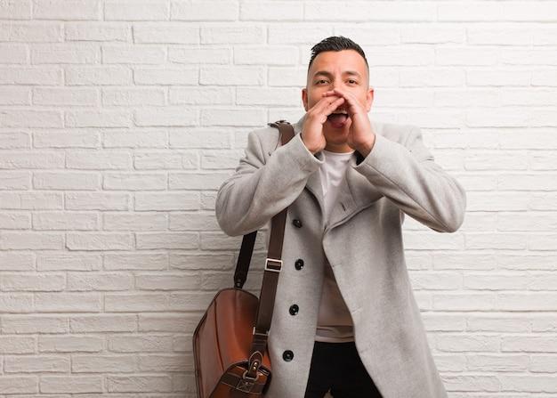 Młody biznesmen łaciński krzyczy coś szczęśliwego do przodu