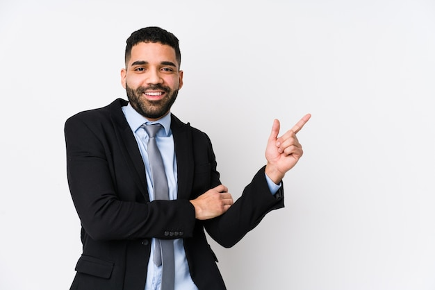 Młody biznesmen łacińskiej uśmiechnięty radośnie, wskazując palcem wskazującym z dala.