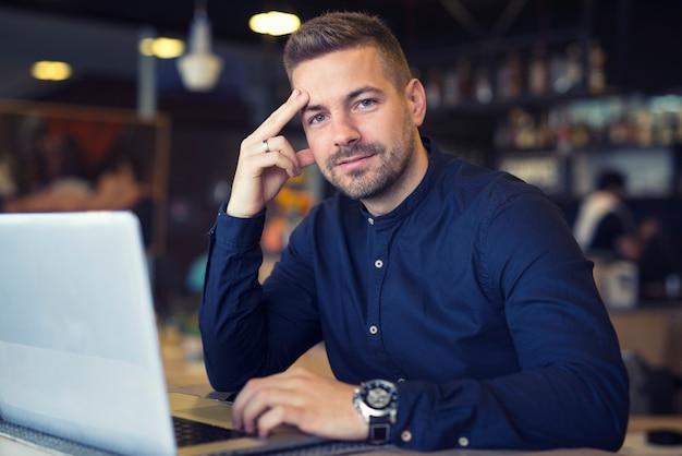 Młody biznesmen lokalizacji w kawiarni z laptopem na stole