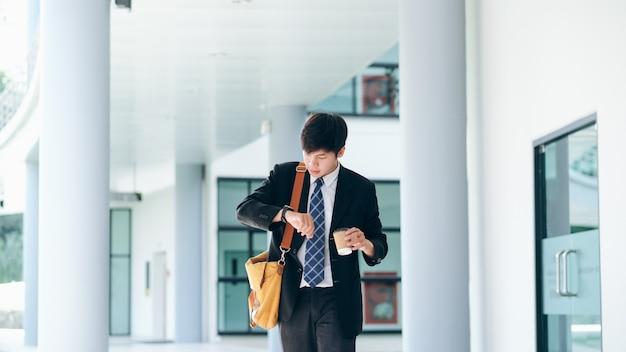 Młody biznesmen martwił się, patrząc na zegarek na rękę.