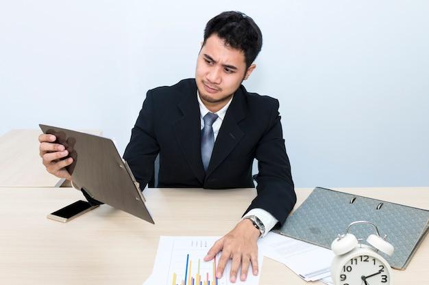 Młody biznesmen męczy i zmartwienia przy biurem.