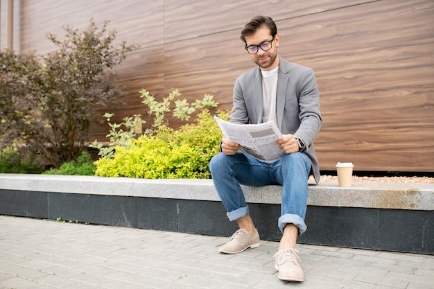 Młody biznesmen miejski w dżinsach i kurtce siedzi w środowisku miejskim i czyta gazetę z najnowszymi wiadomościami