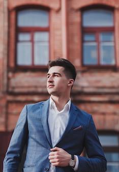 Młody biznesmen. moda młody człowiek w garniturze stojący