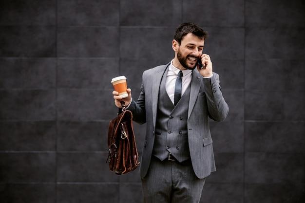 Młody biznesmen modne spaceru po ulicy i przyjemnej rozmowy telefonicznej z kolegą.