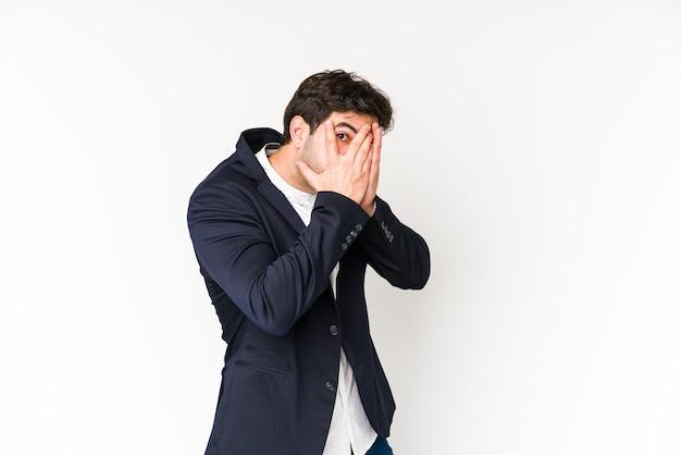 Młody biznesmen mruga przez palce przestraszony i zdenerwowany.