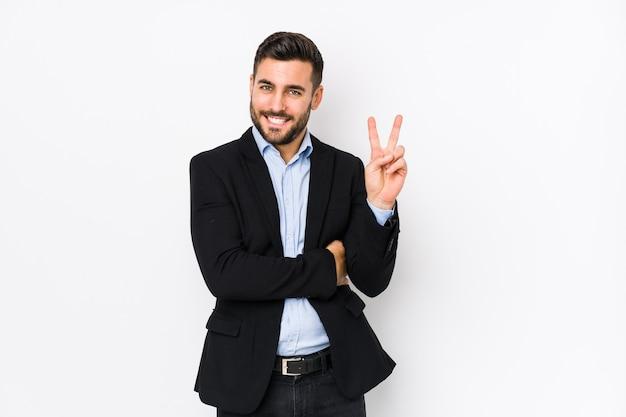 Młody biznesmen na białej ścianie na białym tle pokazuje numer dwa palcami