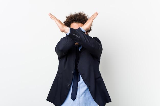 Młody biznesmen na białej ścianie, trzymając skrzyżowane dwa ramiona