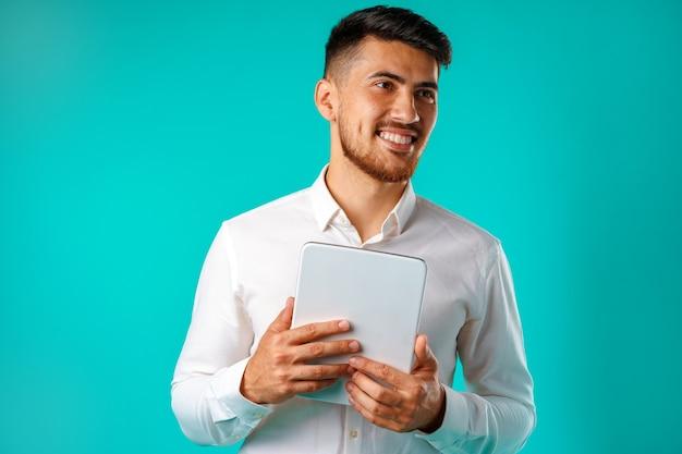 Młody biznesmen na sobie białą koszulę trzyma cyfrowy tablet na białym tle