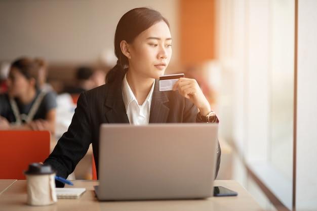Młody biznesmen nosi czarny garnitur przy biurku.