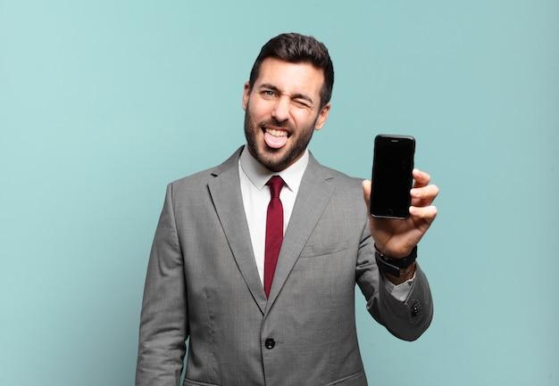 Młody biznesmen o pogodnym, beztroskim, buntowniczym nastawieniu, żartuje i wystawia język, bawi się i pokazuje ekran swojego telefonu