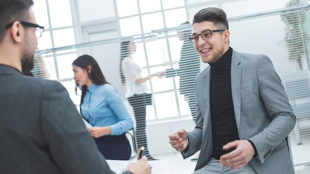 Młody biznesmen omawiając z kolegą swoje pomysły. dni robocze w biurze