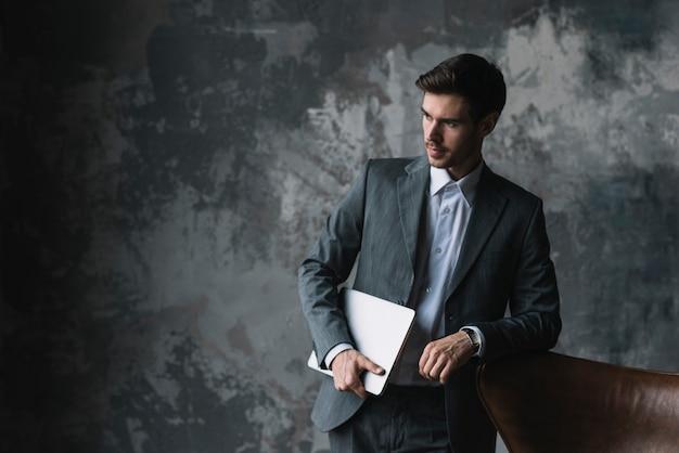 Młody biznesmen opiera na krzesła mienia laptopie w jego ręce przeciw grunge tłu