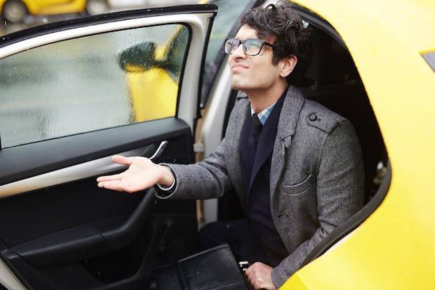Młody biznesmen opuszcza taksówkę w deszczu