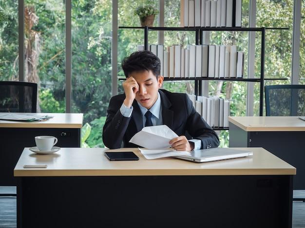 Młody biznesmen otrzymujący złe wieści listem zwolnienia, zmęczony, zestresowany i smutny siedzi z roztargnieniem na biurku w biurze.