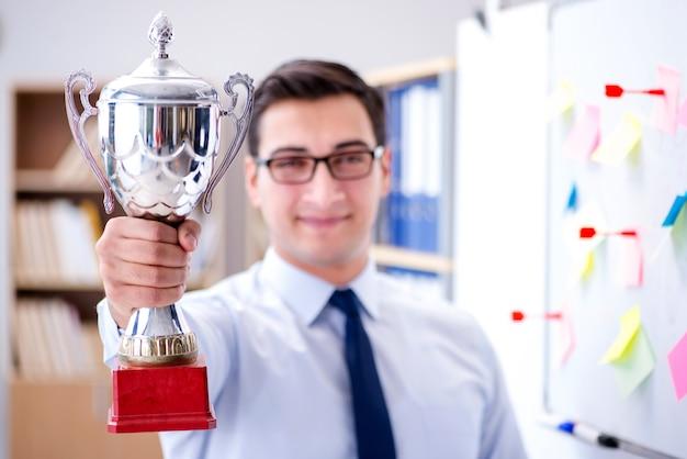 Młody biznesmen otrzymywa nagrodową filiżankę w biurze