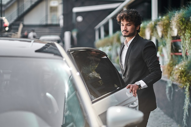 Młody biznesmen otwiera swój samochód.