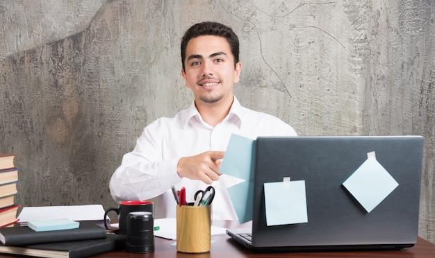 Młody biznesmen patrząc aparatu na biurko.