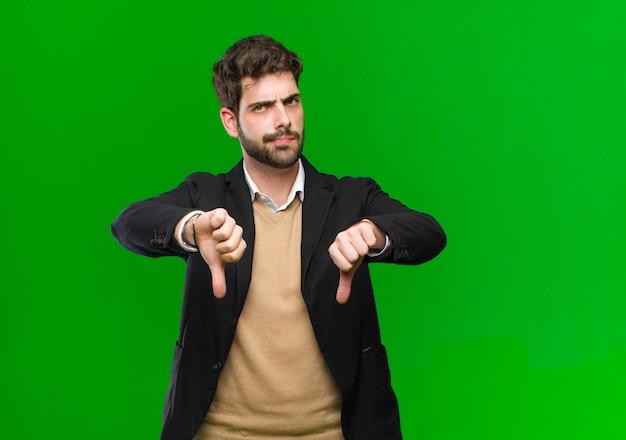 Młody biznesmen, patrząc smutny, rozczarowany lub zły, pokazuje kciuk w dół w nieporozumieniu, czując się sfrustrowany wobec zieleni