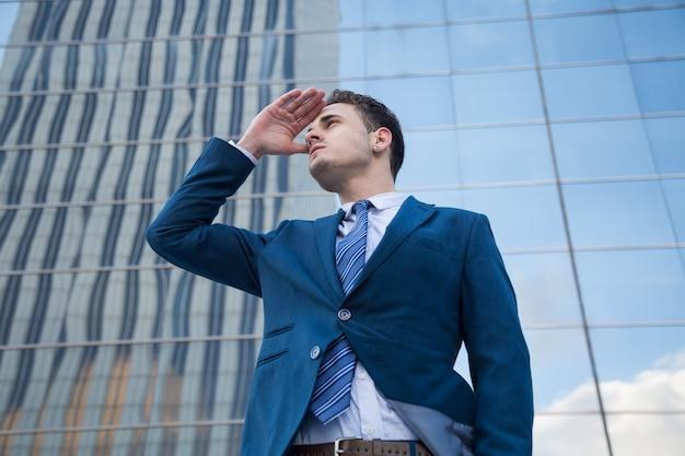 Młody biznesmen patrząc w przyszłość, robiąc gest sukcesu.