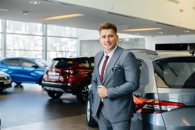 Młody biznesmen patrzy na nowy samochód w salonie samochodowym. kupowanie samochodu.