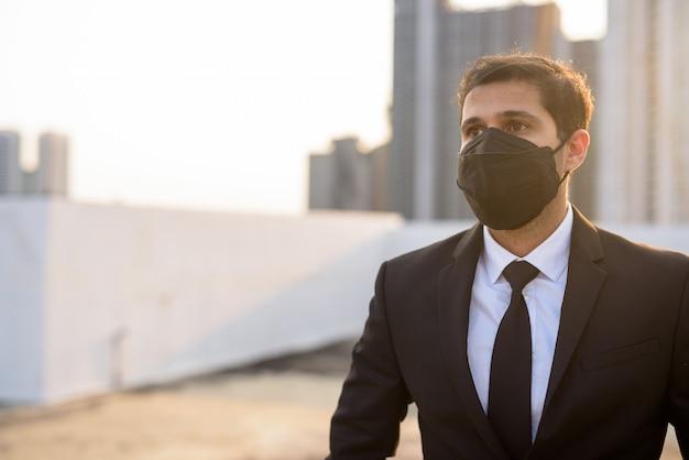 Młody biznesmen perski myśli podczas noszenia maski w celu ochrony przed wybuchem wirusa koronowego i zanieczyszczeniem