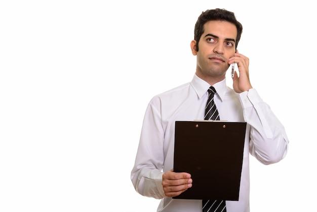 Młody biznesmen perski rozmawia przez telefon komórkowy i trzymając schowek podczas myślenia