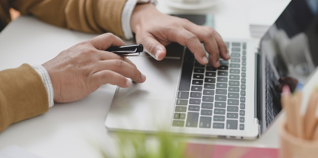 Młody biznesmen pisać na maszynie na laptopie podczas gdy pracujący nad jego aktualnym projektem