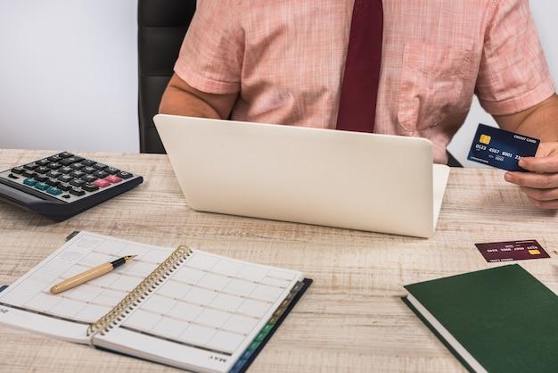Młody biznesmen płaci online kartą kredytową