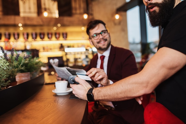 Młody biznesmen płaci zbliżeniową kartą kredytową z technologią nfc.