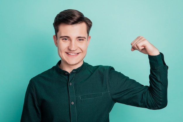 Młody biznesmen pokaż mięśnie ramienia na białym tle na turkusowym tle