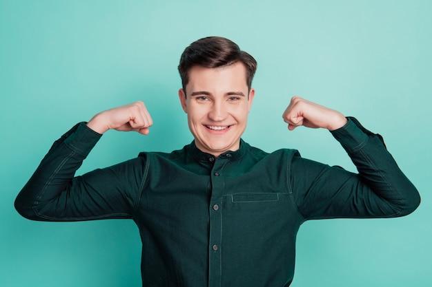 Młody biznesmen pokaż triceps mięśnie ramienia na białym tle na turkusowym tle