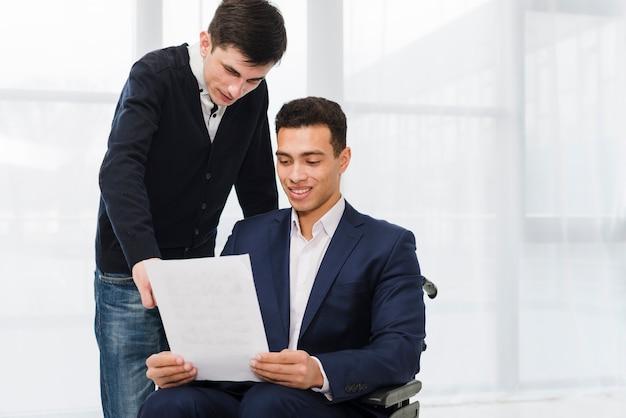 Młody biznesmen pokazuje coś na dokumencie jego kolega siedzi na wózku inwalidzkim