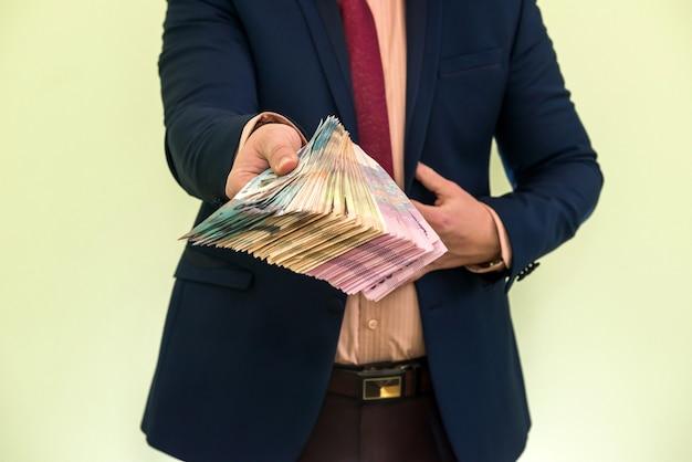 Młody biznesmen posiadający ogromną ilość pieniędzy. nowe ukraińskie banknoty 1000 i 500 uah w rękach biznesmena. zysk.