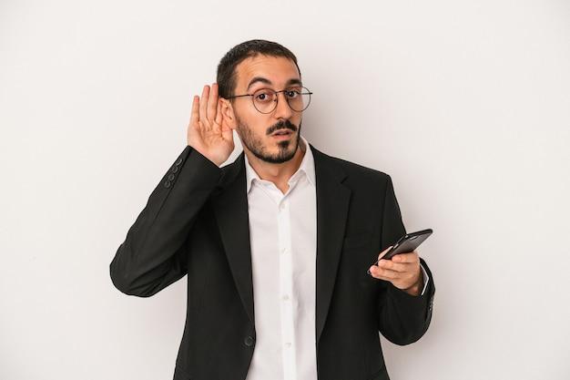 Młody biznesmen posiadający telefon komórkowy na białym tle próbuje słuchać plotek.