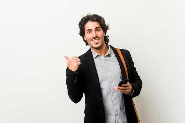 Młody biznesmen posiadający telefon wskazuje kciuk palcem, śmiejąc się i beztroski.